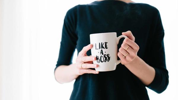"""En kvinne holder et krus som sier """"like a boss"""""""