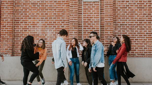 Illustrasjonsbilde av en vennegjeng med 10 personer som står å snakker sammen. Bildet er tatt av Nicolas Lobos fra Unsplash