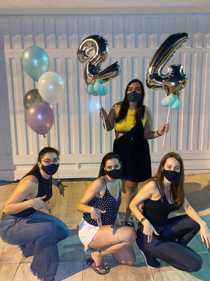 Bilde av fire jenter som har på seg munnbind. Tre sitter på huk, og en står oppreist å holder ballonger