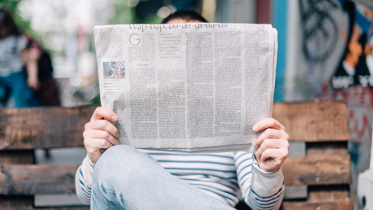 Mann med lys dongribukser og hvit genser med blå striper sitter på en brun benk og leser avisen. Illustrasjonsbilde tatt av Roman Kraft fra Unsplash