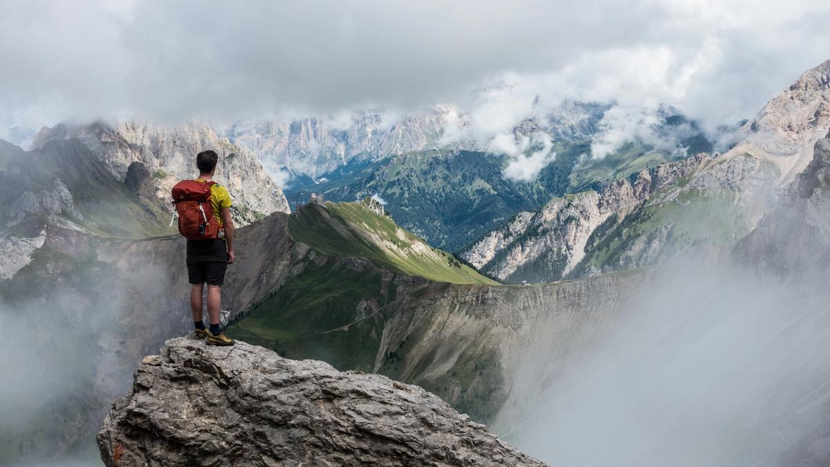 man with red backpack standing on cliff facing mountains under white fog