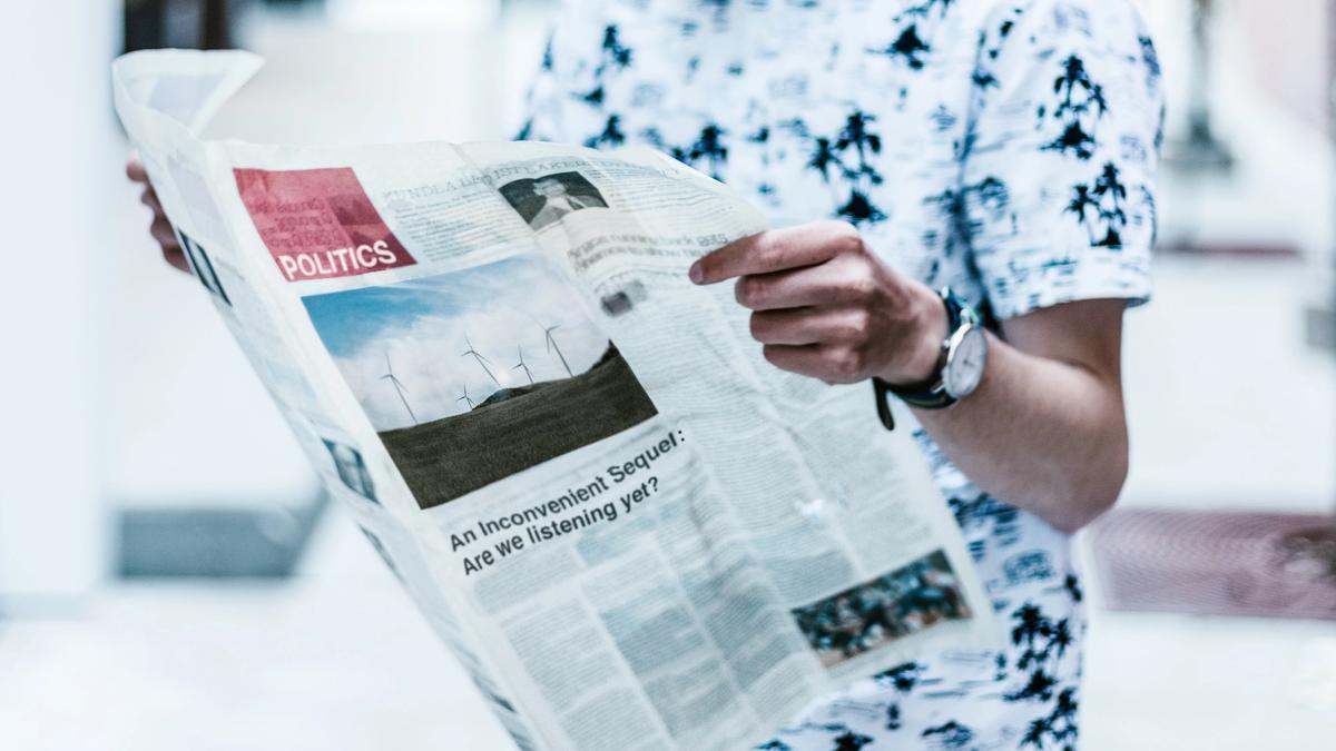 Illustrasjonsbilde av mann i hvit t-skjorte som holder en avis, tatt av Priscilla Du Preez fra Unsplash