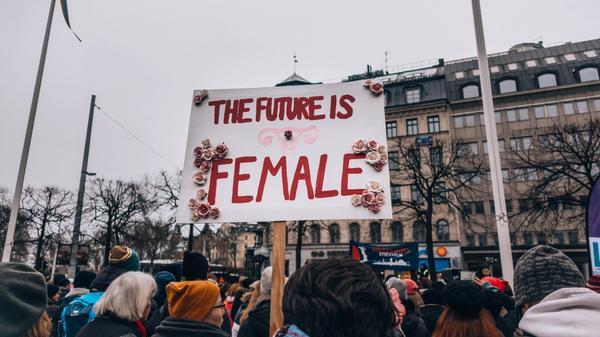 """Illustrasjonsbilde tatt av Lindsey LaMont fra Unsplash av en demonstrasjon hvor noen holder oppe en plakat hvor det står """"the future is female"""""""