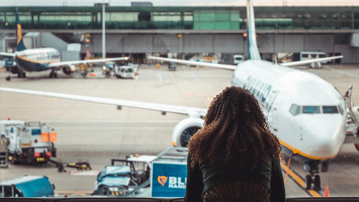 Kvinne sitter på gate på en flyplass