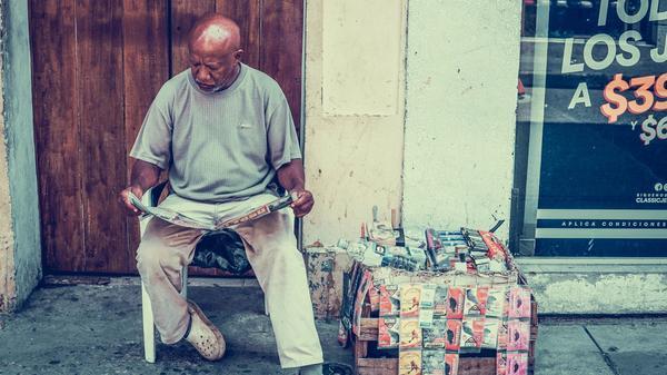 Eldre mann sitter på en stol å leser avisen. Illustrasjonsbilde tatt av Jorge Gardner fra Unsplash