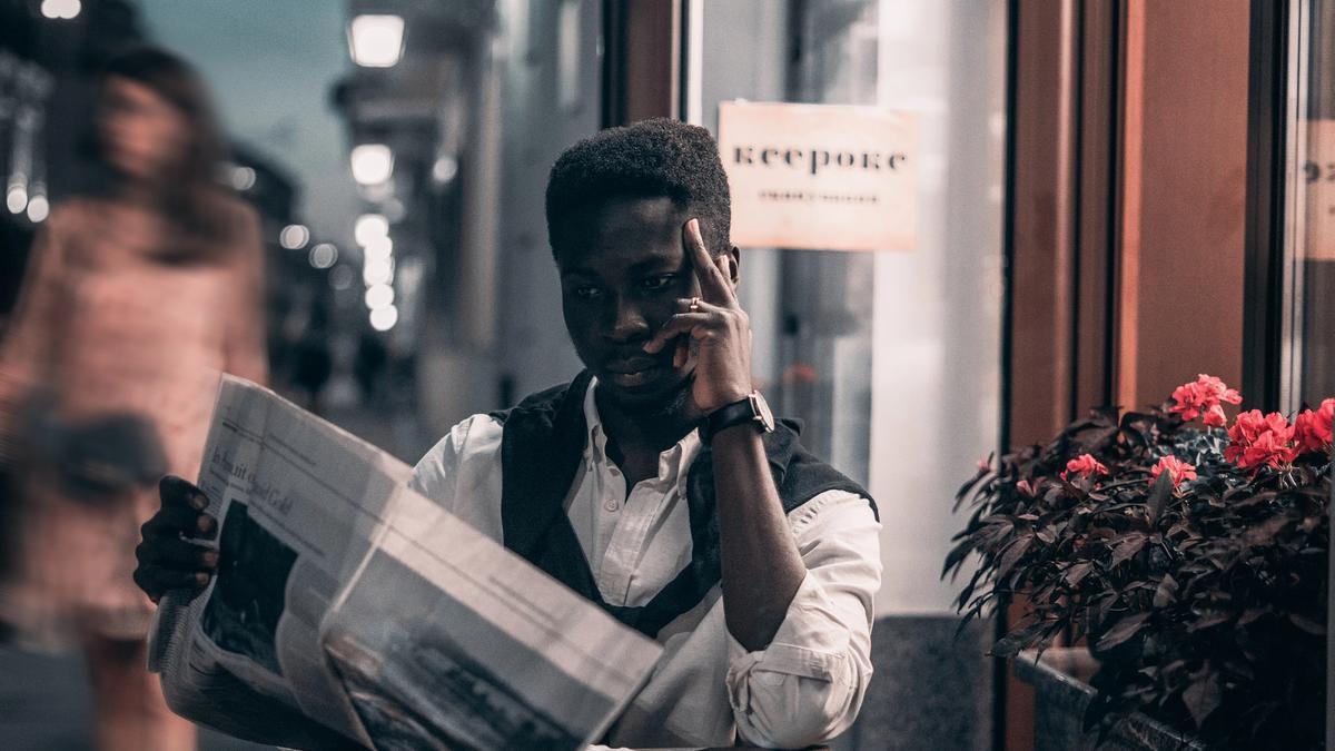Illustrasjonsbilde av en mann som sitter ved et bord å leser avisen,  tatt av Elijah O'Donnell fra Pexels