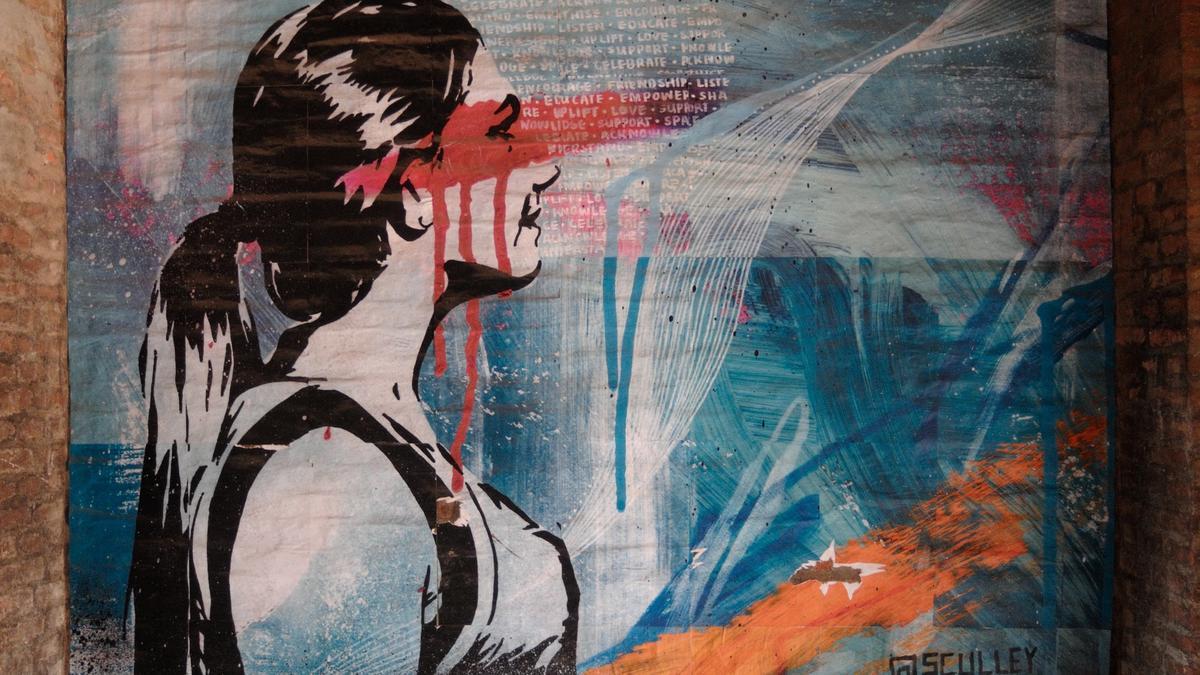 Maleri på en utendørsvegg av en ung kvinne med mørkt langt hår og rød maling over øynene. Illustrasjonsbilde tatt av Tobi Feder fra Unsplash