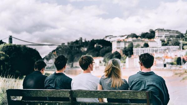 Fem personer sitter på en benk og ser mot en by som ligger på andre siden av elven. Illustrasjonsbilde tatt av Matthew Gerrard fra Unsplash