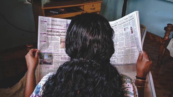 Illustrasjonsbilde av kvinne med mørkt hår som leser en avis. Bildet er tatt av Abhijith S Nair fra Unsplash