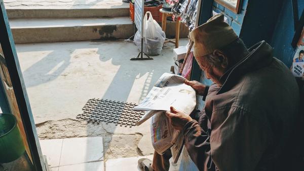 Eldre Nepalsk mann som leser avisen. Illustrasjonsbilde tatt av Mohan Khadka fra Unsplash