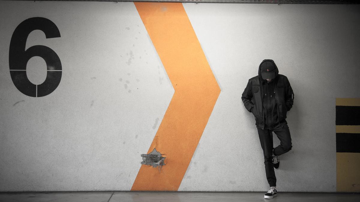 Ung mann står alene i et parkeringshus
