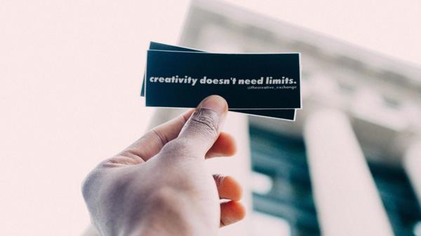 """Illustrasjonsbilde av en hånd som holder opp en svart lapp hvor det står skrevet i hvitt : """"creativity doesn´t need limits"""""""