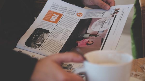 En person leser avisen med en stor kaffekopp