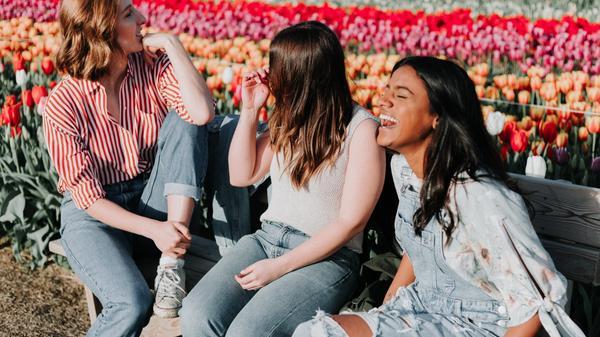 Tre kvinner som sitter på en benk med tulipaner i bakgrunnen. Illustrasjonsbilde tatt av Priscilla Du Preez fra Unsplash