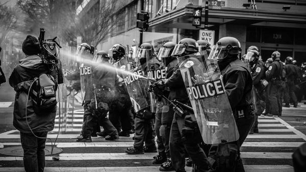Politi i en rekke. Den ene sprayer tåregass.