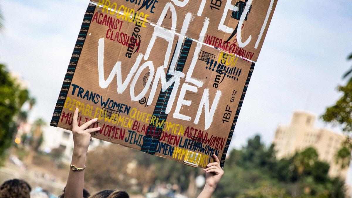"""Kvinne holder ett skilt som sier """"respect all women"""" i en demonstrasjon"""