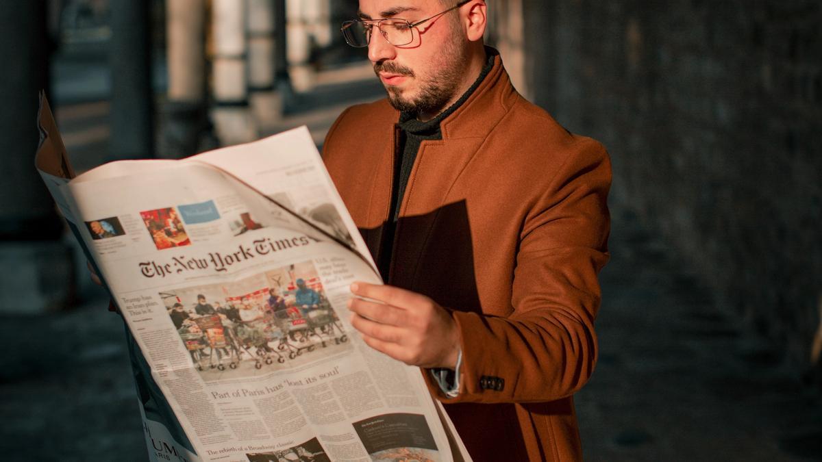 Illustrasjonsbilde av en ung mann med brun kåpe som står å leser en avis, tatt av Ömer Faruk Tokluoğlu fra Unsplash