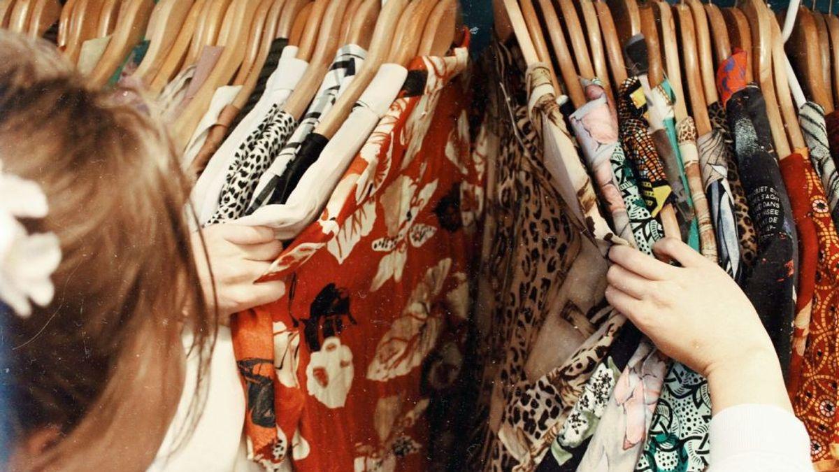 Bilde av kvinne som ser på mange fargerike klær som henger på et klesstativ. Illustrasjonsbilde tatt av Becca McHaffie fra Unsplash