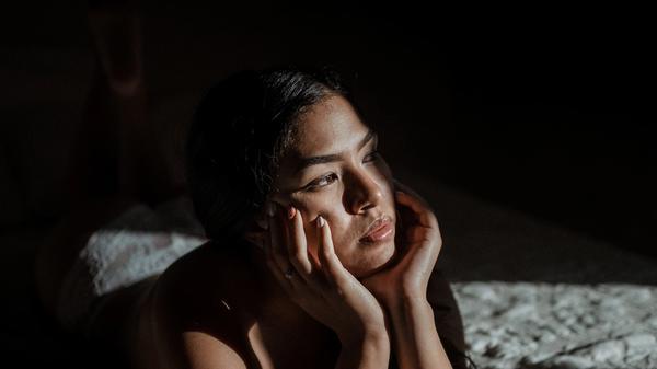 Jente som ligger i en seng og ser utover