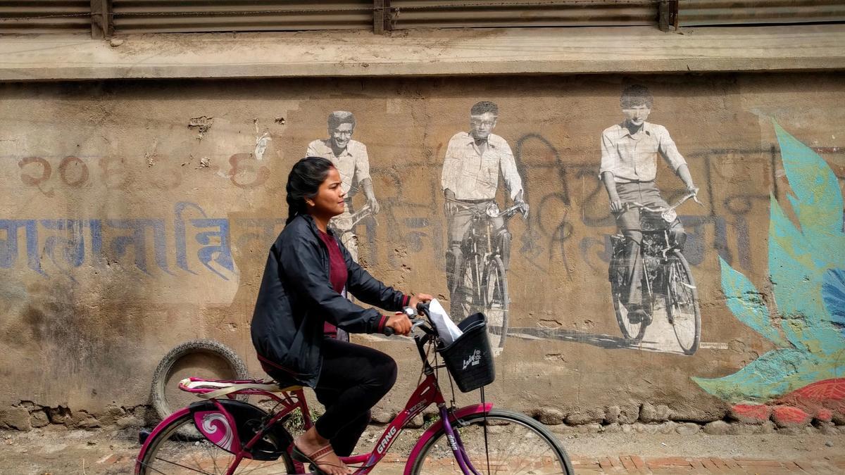 En nepalsk jenter sykler i en gate
