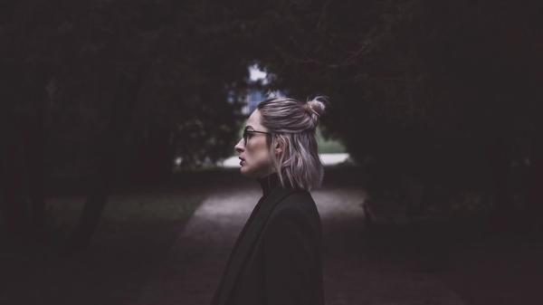 Kvinne står i en gate og ser alvorlig til venstre