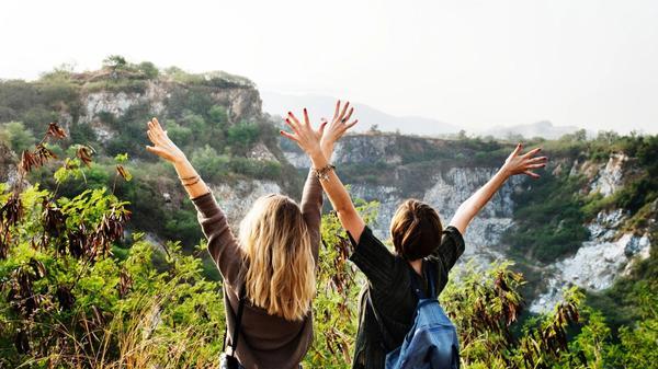 To venner står ute i naturen med hendene i været