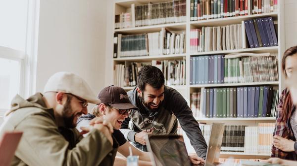 Illustrasjonsbilde av tre menn som smiler mens de peker og ser på en laptop, tatt av Priscilla Du Preez fra Unsplash