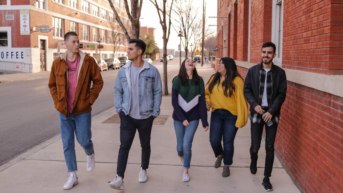 Illustrasjonsbilde av en gruppe ungdommer som går sammen i en by og snakker og flirer sammen. Bildet er tatt av Eliott Reyna fra Unsplash