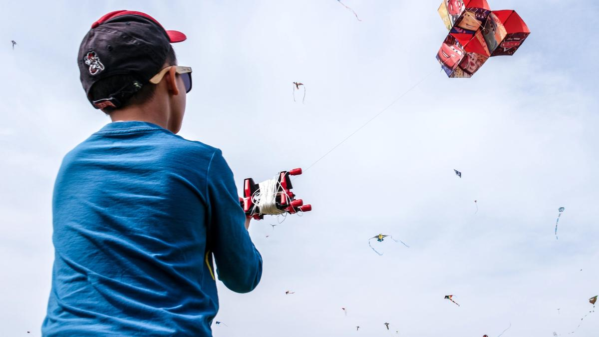 Gutt i blå genser og caps som leker med drager. Illustrasjonsbilde tatt av Rene Vincit fra Unsplash