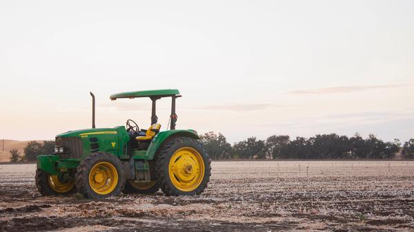 Grønn traktor som står på et jorde. Illustrasjonsbilde tatt av Nathan Lugo fra Unsplash