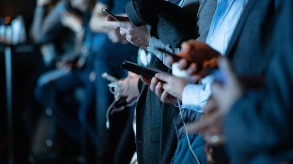 Illustrasjonsbilde av personer mange personer på rad i mørke dresser som holder mobilene sine tatt av camilo jimenez fra Unsplash