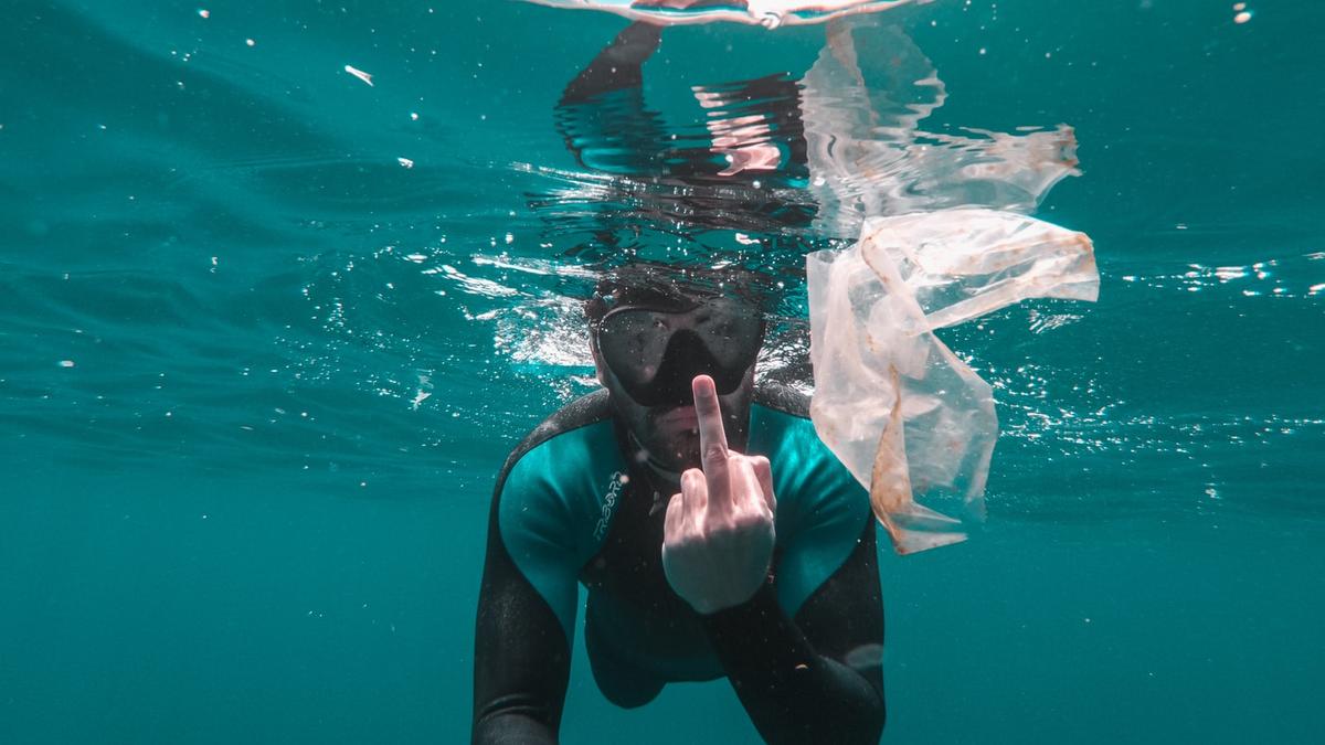 Bilde av en som dykker i havoverflaten, og viser fingeren til en plastpose i vannet.