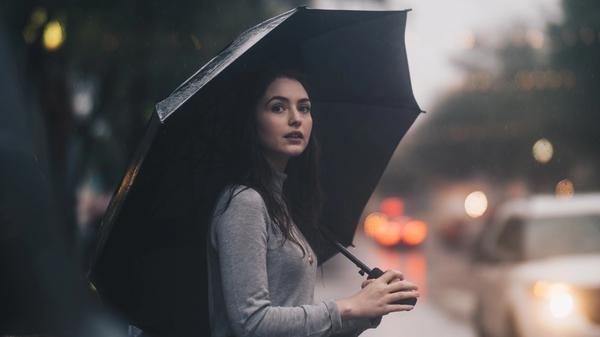 Kvinne står ute i regnet med en paraply