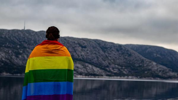 Kvinne med regnbueflagg over skuldrene. Bilde tatt av Karoline Skarstein