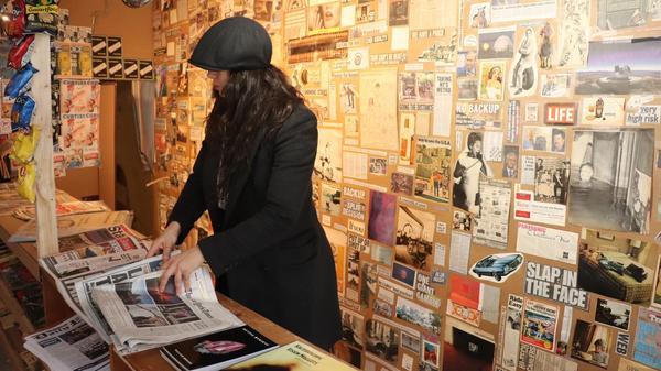 Kvinne med svart hatt som holder mange aviser, illustrasjonsbilde tatt av Kat Coffe fra Unsplash