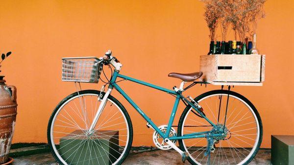 Bilde av en turkis sykkel med en trekasse med blomster i. Bakgrunnen er orange. Illustrasjonsbilde tatt av Sagar Rana fra Unsplash