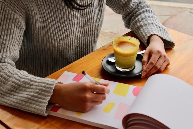 Kvinne som sitter med en kaffelatte og notatbok Illustrasjonsbilde tatt av Freshh Connection fra Unsplash