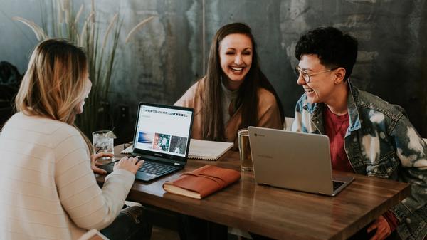 Illustrasjonsbilde av tre unge personer, en gutt og to jenter, som sitter å smiler mens de studerer, tatt av Brooke Cagle fra Unsplash