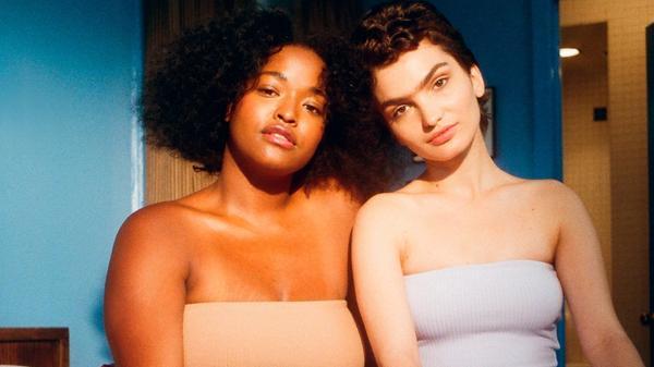 To vakre kvinner som sitter i en seng