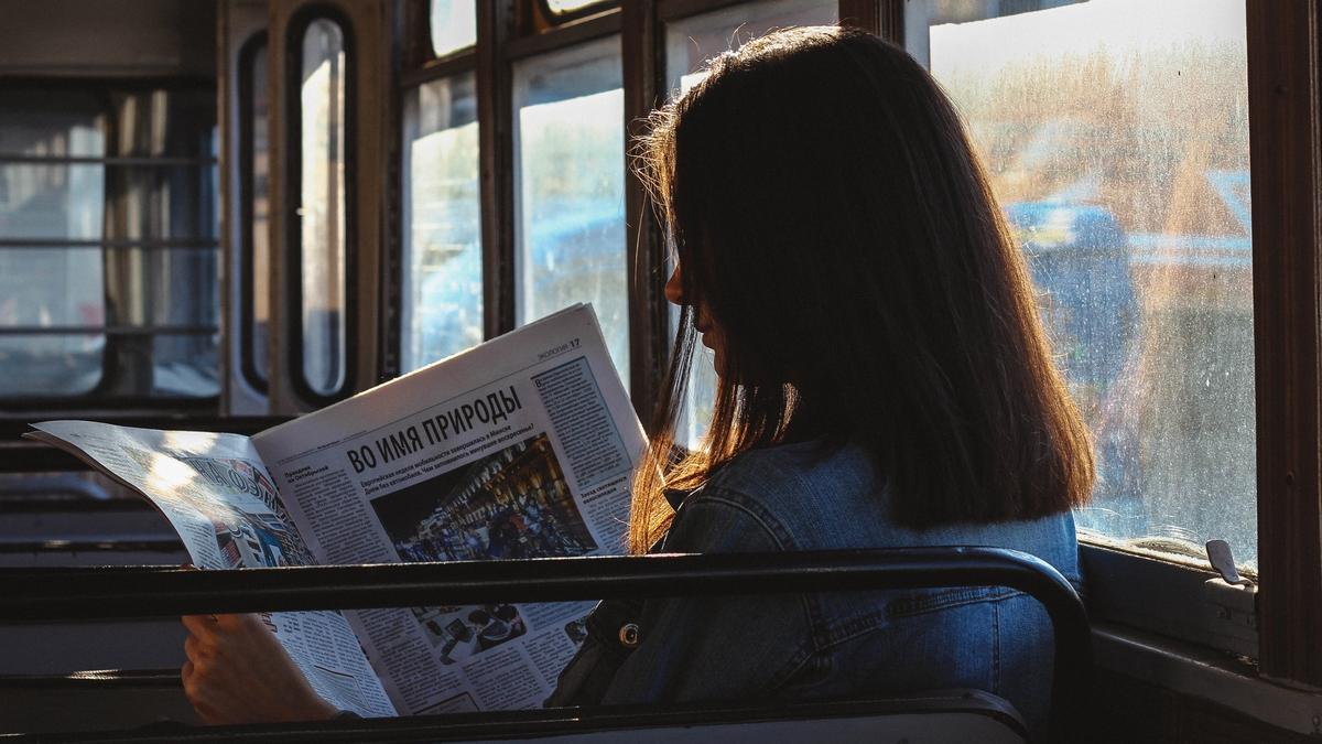 Illustrasjonsbilde av en kvinne som leser avisen på en buss tatt av Artem fra Pexels