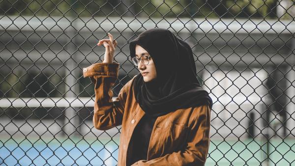 Jente med svart hijab og brun jakke