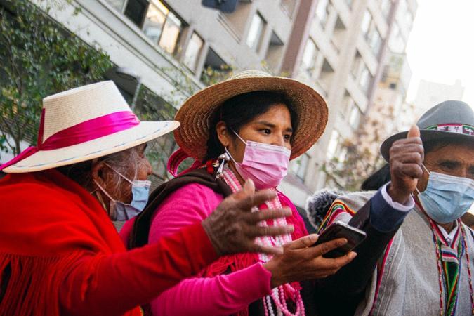 En ung kvinne i rosa klær står mellom en eldre kvinne i røde klær og en hvit hatt med en rosa sløyfe og en gammel mann. Bilde tatt av Isidora Alejandra Torrealba