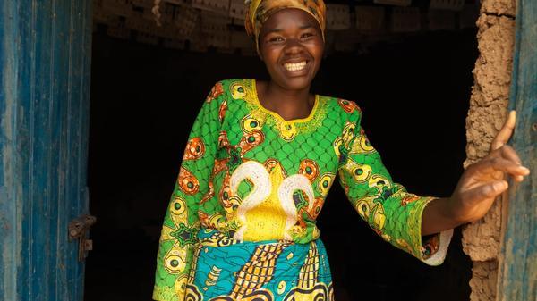 En kvinne som står i en døråpning og smiler. Hun har på seg grønn fargerik bluse og et turkis skjørt. Bilde tatt i Rawanda av Care. Publisert med tillatelse fra Care.