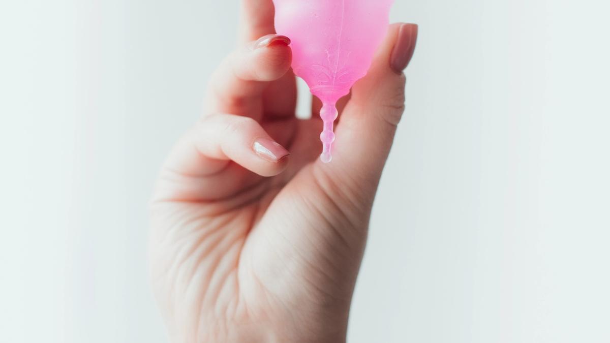 En hånd som holder en rosa menskopp