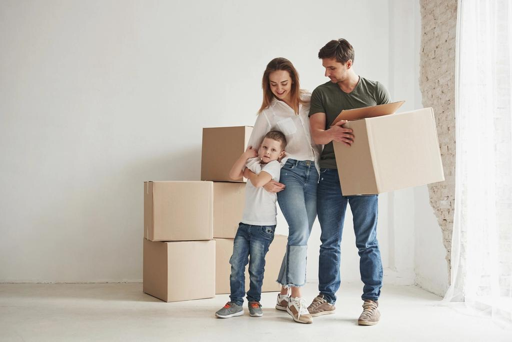 Family holding moving boxes