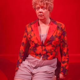 Performer with camouflage on red background