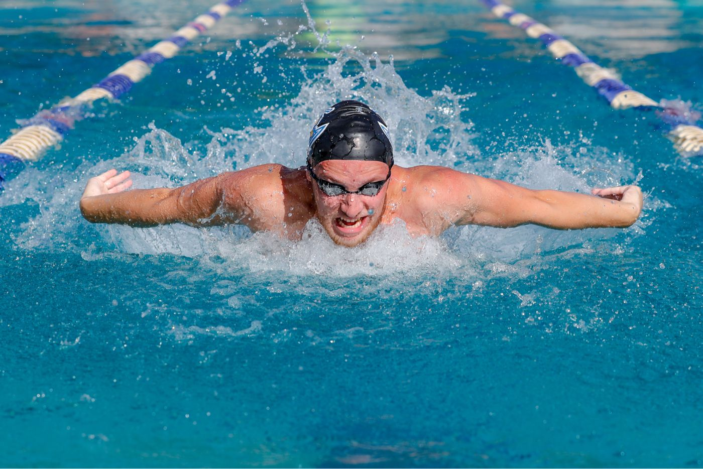An athlete swimming in the pool competitively during a swim meet.