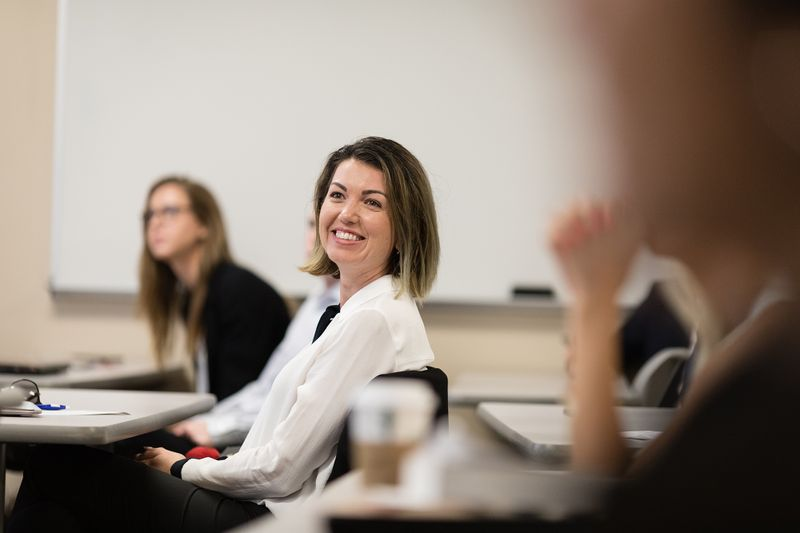A student smiles in a business course.