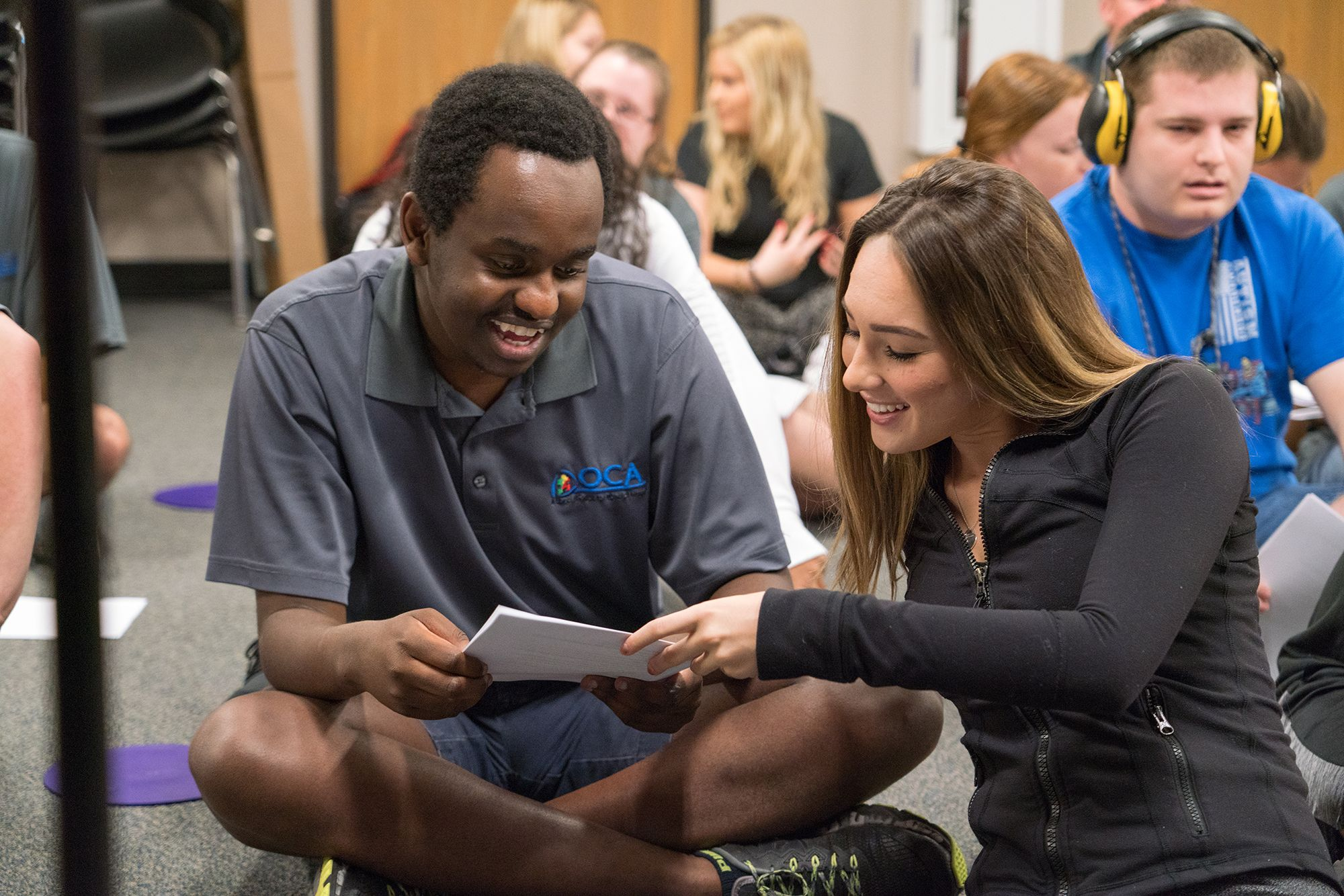 A college student looks at a play script with a person with autism.