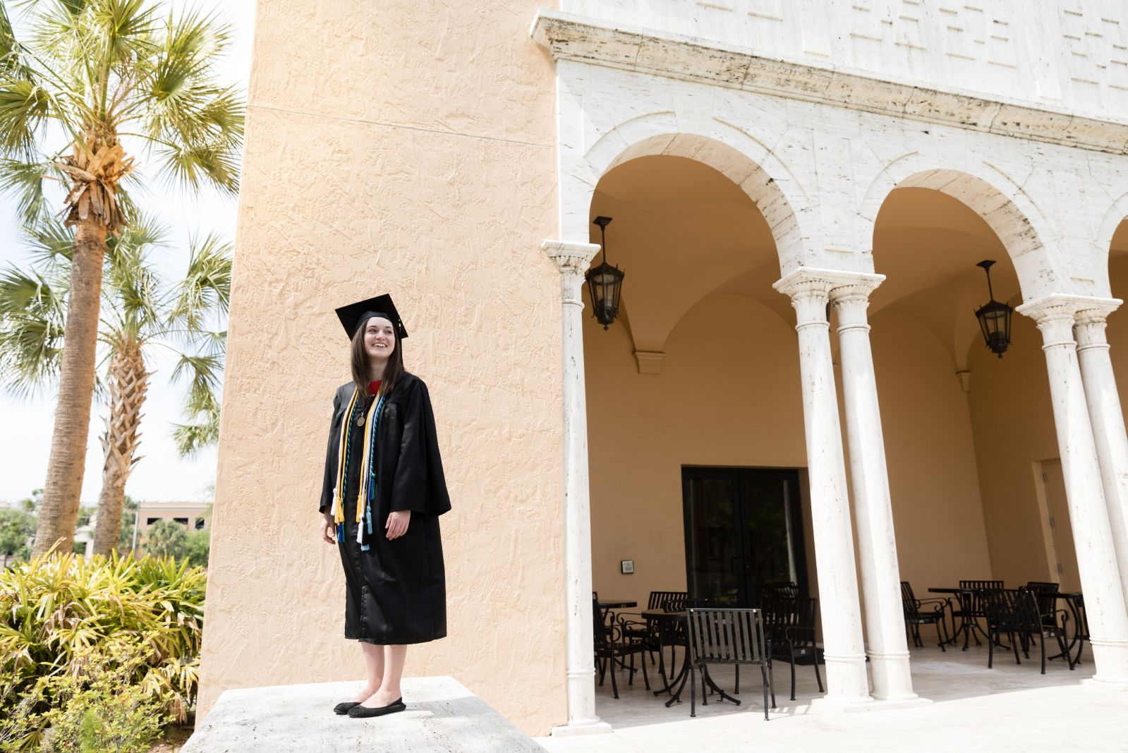 Female college student poses in a cap and gown outside the Bush Science Center.